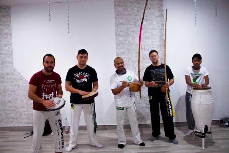 el profesor de capoeira con sus alumnos con los instrumentos de capoeira