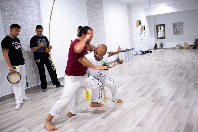 profesor de capoeira y alumno haciendo el baile de capoeira